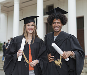 Photo of a young man and woman in graduation gowns and caps holding their diplomas